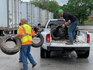 two men unloading old tires from a white pickup
