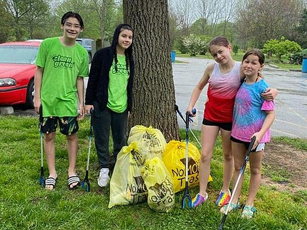 group of four young people standing with trash bags they filled