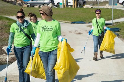 four ladies carrying bright yellow trash bags full of trash they picked up